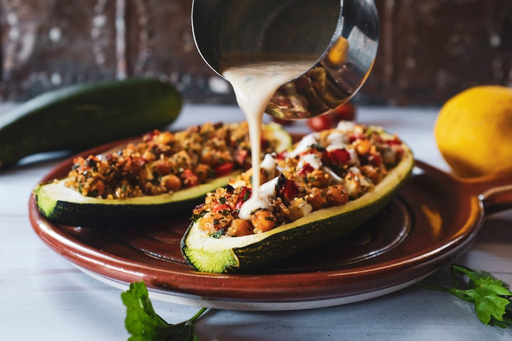 Pouring tahini sauce over Middle Eastern stuffed zucchini boats